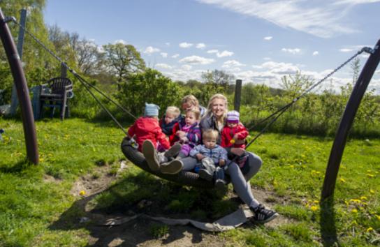 Sabine Asmussen und Doreen Biehl auf einer Schaukel mit Kindern