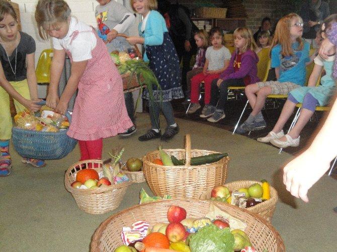 Kinder bringen Erntegaben zum Altar